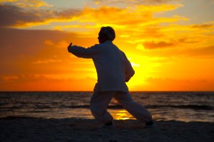 Chinese Elderly Woman Performing Taichi Outdoor by the beach und