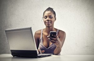 A beautiful black woman is smiling while is using a smart-phone