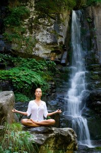 Beautiful young woman meditating in lotus position while doing y