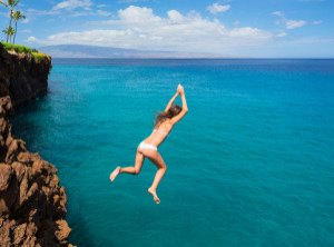 Woman jumping off cliff into the ocean. Summer fun lifestyle.