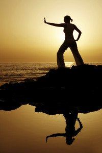 Yoga woman silhouetted against the setting sun with a natural reflection in a rockpool