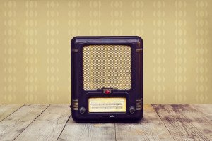 Retro radio on a wooden floor over vintage wallpaper. Toned image