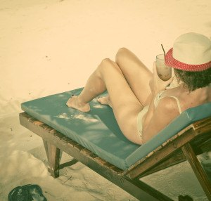 Woman sunbathing on beach chair, Thailand - retro style postcard