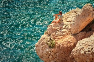 Young Man Relaxing On Rocky Cliff With Blue Sea On Background Su