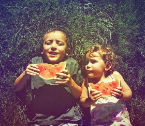 two kids eating watermelon done with a retro vintage instagram filter