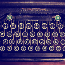 an antique typewriter on a wooden table toned with a retro vinta