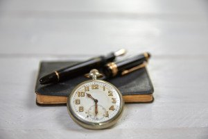Antique fountain pen old calendar and watch on a white wooden table