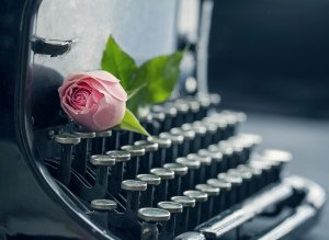 Old antique black vintage typewriter with a pink romantic rose